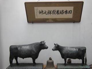 掛け軸と乳牛の像